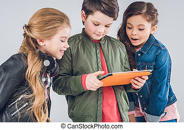 Three cute little kids using digital tablet together on grey