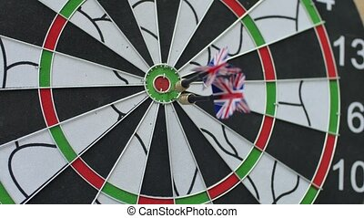 Three darts hitting the bullseye of the dartboard and one missing