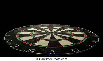 Low angle on dartboard with three darts including bulls eye