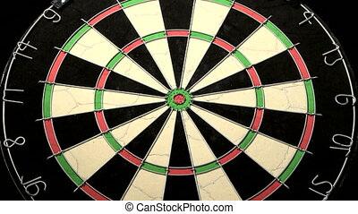 Three darts hit a dartboard including the bulls eye