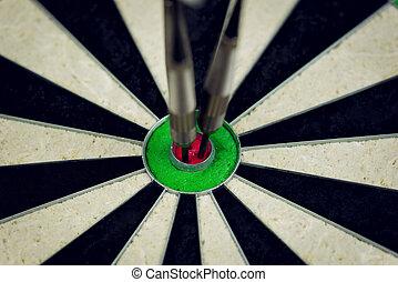 bulls eye - three darts thrown at the bulls eye of a...