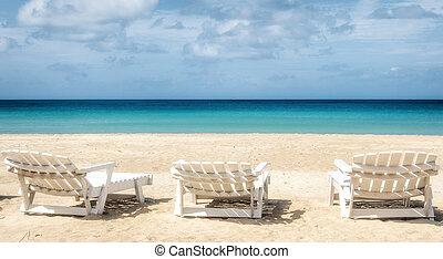 Three deckchairs facing out to sea on idyllic beach