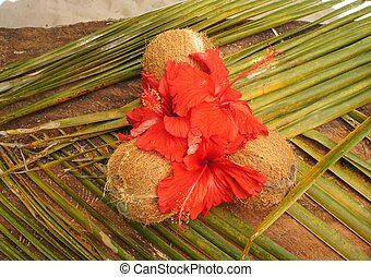 three decorated coconut with red flower on a palm leaf
