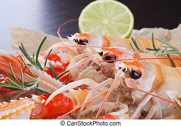 Three Delicious Grilled Langoustines with Lime and Rosemary closeup on Dark Wooden background. Focus on Foreground