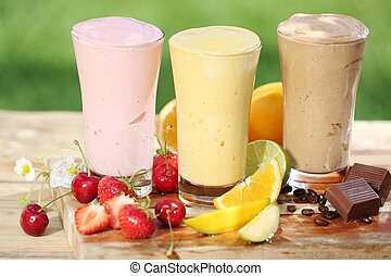 Three delicious smoothies with yoghurt or ice cream blend, two made with fruit and one of chocolate, together with various fresh tropical fruit on a garden table