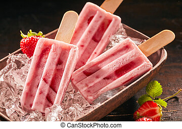 Three delicious summer snacks. Delicious frozen ice cream popsicle or ice lollies with strawberry and yoghurt on rustic plate.