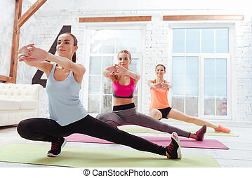 Three delighted women doing fitness exercises together