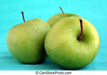Three deluxe green apples on green background