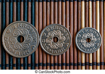 Three Denmark coins denomination is 5, 2 and 1 krone (crown) lie on wooden bamboo table, good for background or postcard
