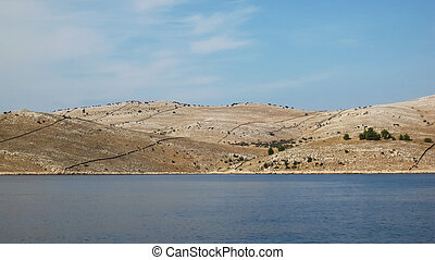 Three desert hills of Kornati islands that overlap at hot sunny day