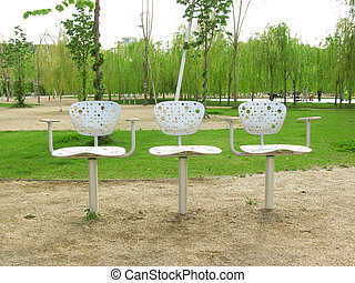 Three design chairs in a park