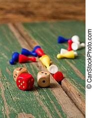 Three dices and color figurines on old wooden board