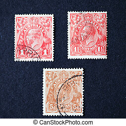 Three different vintage Australian postage stamps of one, one and a half and five pence with head of King George the fifth.