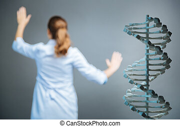 Three dimensional model of dna with scientist working in background