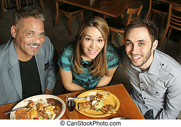 High angle shot of three people dining at a Mexican restaurant.