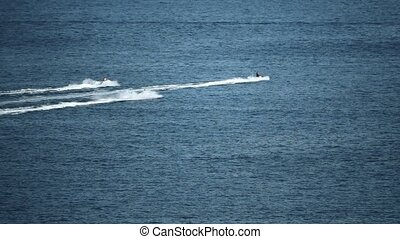 Three distant jet ski riders at sea, slow motion shot -...
