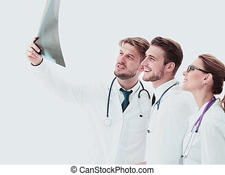 Three doctors looking attentively at x-ray and discussing it...