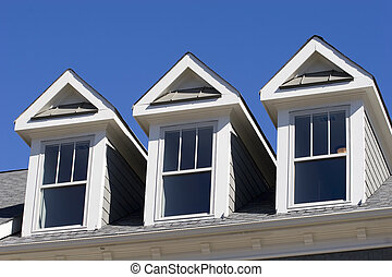 Three Dormers - A roof line with three dormers against a...