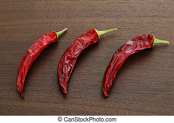 Three dried hot red chili peppers