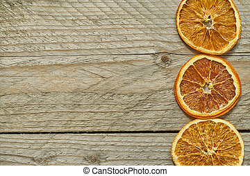 three dried orange slices on wooden background, top view, copy space