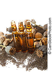 Three drug ampoules on the pile of poppys seeds and poppy heads