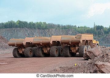 three dumper trucks in a row in a quarry mine.