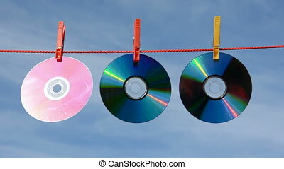 three dvd and cd discs on string