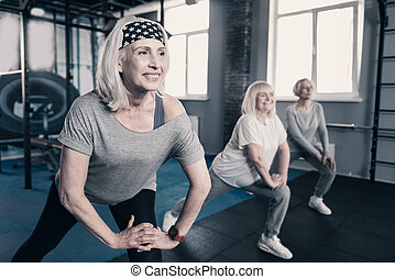 Three elderly women doing lunges in gym