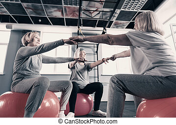 Three elderly women holding hands while sitting on exercise balls