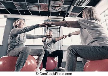 Three elderly women holding hands while sitting on exercise balls