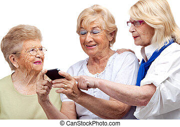 Three elderly women with cellphone. - Close up portrait of ...