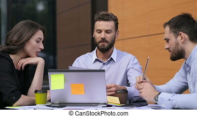 Three employees working on business project.