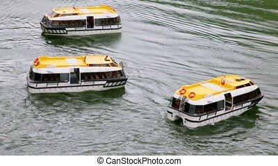 Three empty passengers transport vessels swing on water...
