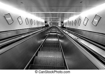 three escalators, going down view, black and white photo