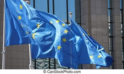 Three EU flags fluttering at European Commission house on a...