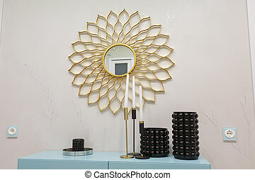Three even vases stand on a blue stick. On the wall, a round mirror looks like the sun.