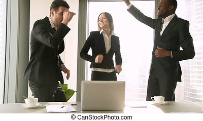 Three excited business people dancing in the workplace, celebrating victory