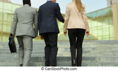 Group of three business executives walking upstairs to a modern building