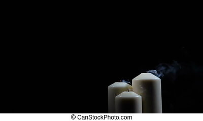 Three extinguished candles with smoke on a black background