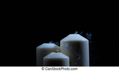 Three extinguished candles with smoke on a black background....