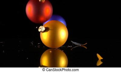 three falling and broken christmas balls on black...