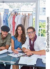 Three fashion designers smiling