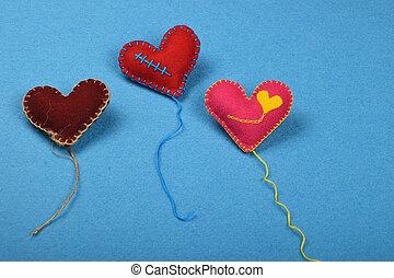 Three felt craft art hearts with threads on blue