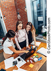 Three female college students working on assignment together using laptop standing at home