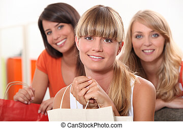 three female friends at home with shopping bags