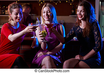Three female friends enjoying drinking