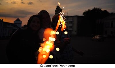 Three female friends having fun and playing with firework candles