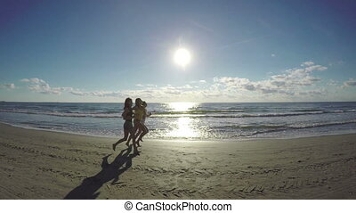 Three female friends jogging during workout on the beach along the sea