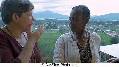Three female friends over 60 talking outside overlooking a mountain view