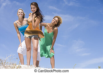 Three female friends relaxing at beach against blue sky